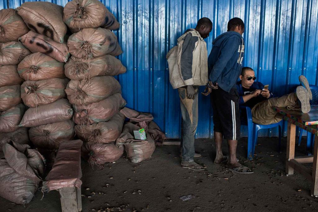 Ένας ασιάτης εργάζεται σε ένα κατάστημα καταμέτρησης κοβαλτίου και υπολογίζει μια πληρωμή, ενώ σκαφείς κοιτούν με ανυπομονησία, στην αγορά της Musompo. Φώτο από Michael Robinson Chavez.