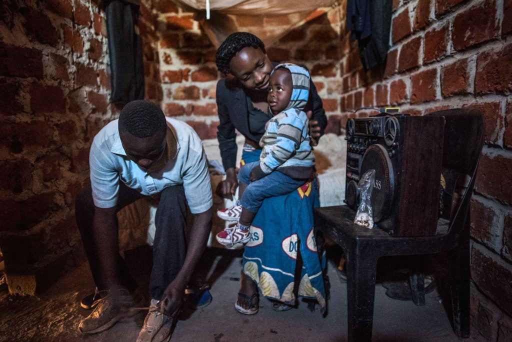 "KOLWEZI, DEMOCRATIC REPUBLIC OF CONGO - JUNE 10 Sadiki Muyumba(cq), left, puts on his shoes in the room he shares with his wife Ivette Mujombo Tshatela and their 2-year-old son Harold Muhiya Mwehu in Kolwezi on June 10, 2016. Muyumba is a ""creuseur,"" or digger who works in the cobalt and copper mines that surround Kolwezi. Like most miners, he works in harsh conditions to bring home $2-3/day. Muyumba and his family rent part of an unfinished home and have no electricity or running water. Cobalt is used in batteries for electronic cars and mobile phones and the DRC has roughly 65 percent of the world's supply. (Michael Robinson Chavez/The Washington Post)"