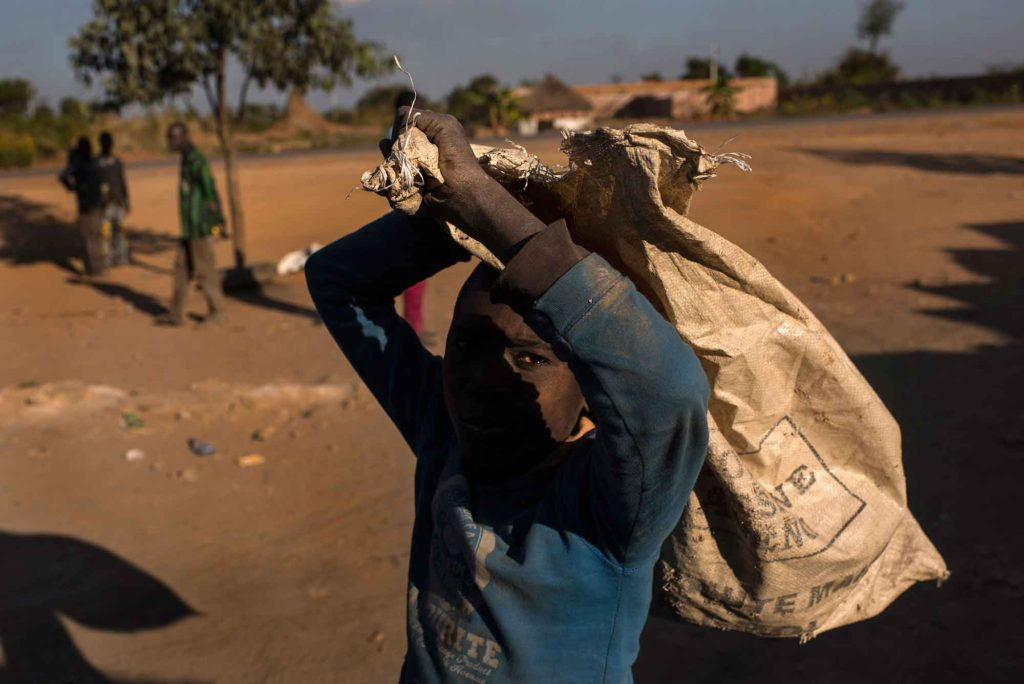 KOLWEZI, DEMOCRATIC REPUBLIC OF CONGO - JUNE 7 A boy carries a bag used to transport cobalt laden dirt and rock at Musompo, a mineral market outside Kolwezi on June 7, 2016. The cobalt dug up by the diggers is sold to Congo Dongfang International Mining(CDM). Cobalt is used in batteries for electronic cars and mobile phones and the DRC has roughly 65 percent of the world's supply. Child labor, unsafe working conditions and contamination are all evident in the cobalt mining process. (Michael Robinson Chavez/The Washington Post)