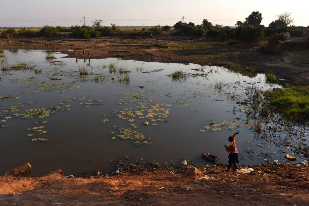 KAPOLOWE, DEMOCRATIC REPUBLIC OF CONGO - JUNE 10 A child throws a stone into the Kapolowe River outside Lubumbashi on June 10, 2016. Environmentalists, doctors and activists say that the region's rivers suffer from severe pollution which they believe is from the copper and cobalt mining operations throughout the area. Fish from the waterways is a staple in the local diet as are the crops grown using the local water. Cobalt is used in batteries for electronic cars and mobile phones and the DRC has roughly 65 percent of the world's supply. (Michael Robinson Chavez/The Washington Post)